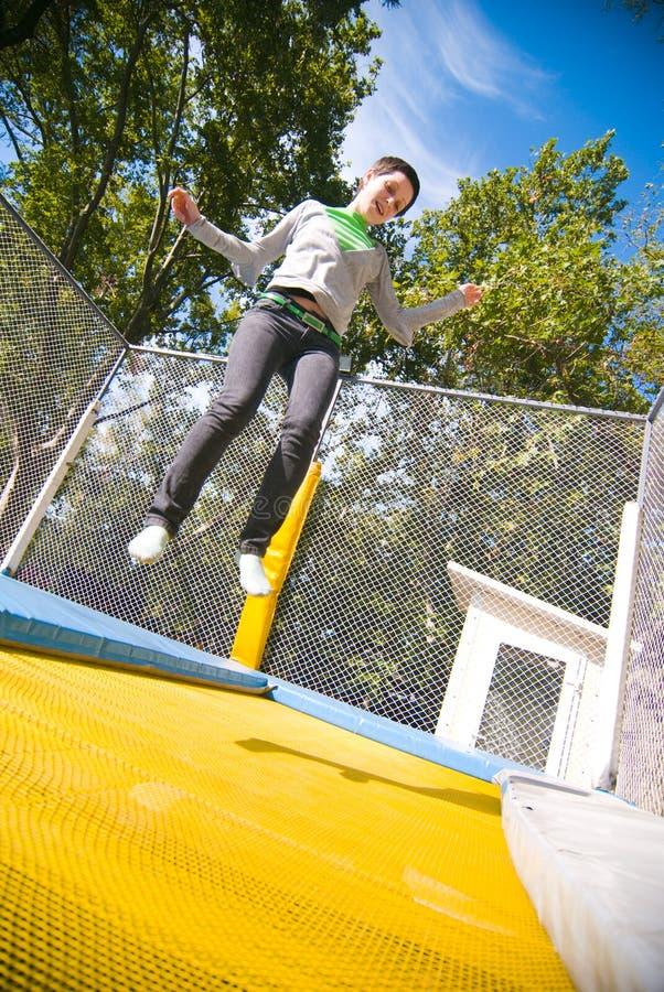 Tiener die op trampoline springt stock foto's