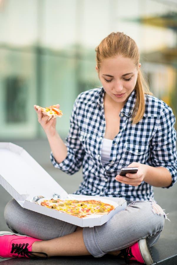 Tiener die pizza eten die in telefoon kijken royalty-vrije stock afbeelding