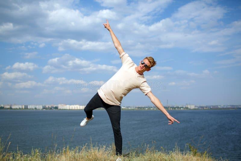 Tiener die pret hebben dichtbij de rivier Een modieuze jonge kerel op een natuurlijke achtergrond Toevallig manierconcept De ruim royalty-vrije stock foto's