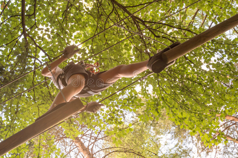 Tiener die pret op hoge kabelscursus hebben, avontuur die, park, bomen in een bos beklimmen stock foto