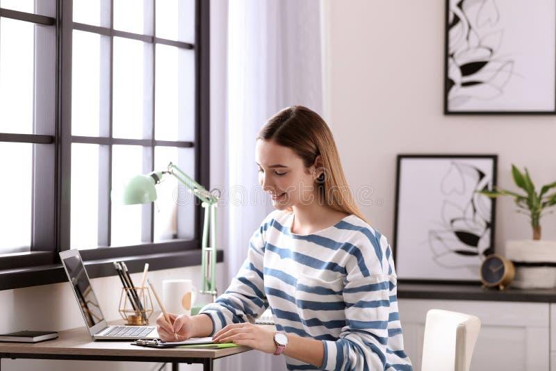 Tiener die thuiswerk doen bij lijst stock fotografie