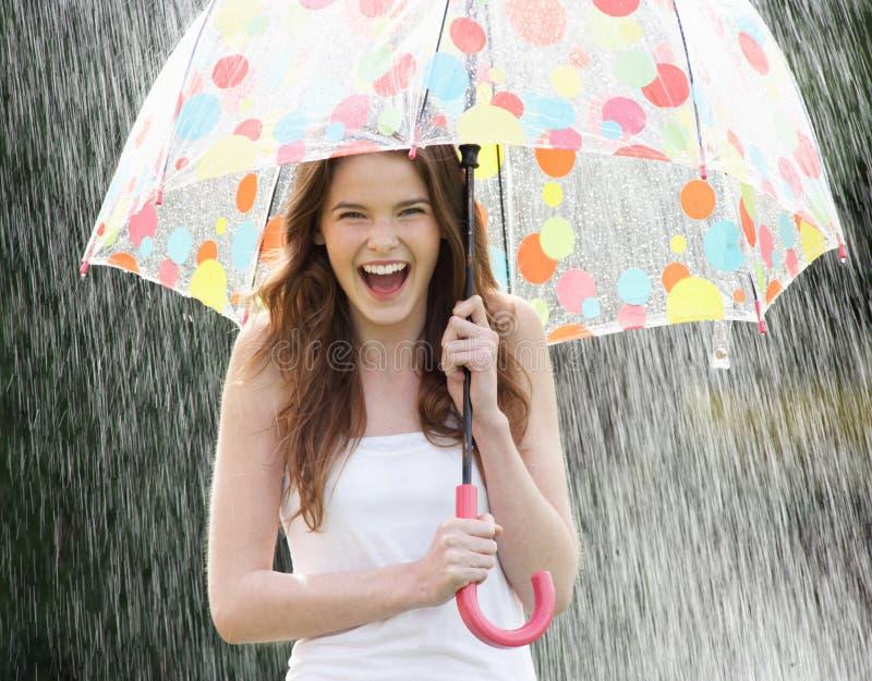 Tiener die van Regen onder Paraplu beschutten stock afbeelding
