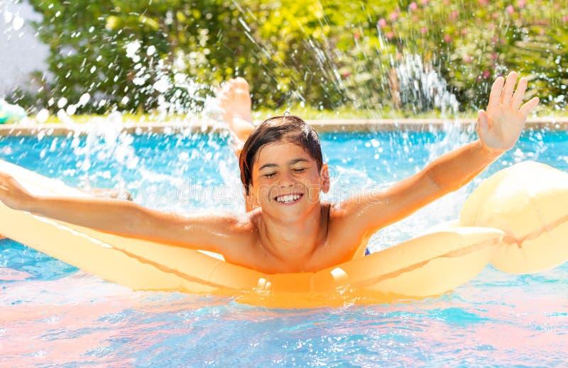 Tiener die van zomer in zwembad genieten stock foto