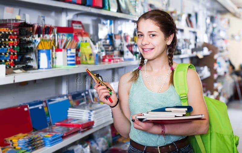 Tiener die verschillende producten in kantoorbehoeftenwinkel kopen stock foto