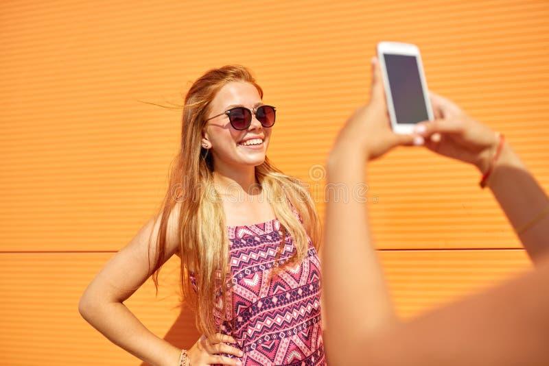 Tiener die vriend fotograferen door smartphone stock fotografie