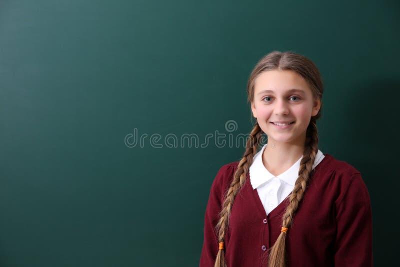 Tiener die zich dichtbij groen schoolbord bevinden stock afbeelding