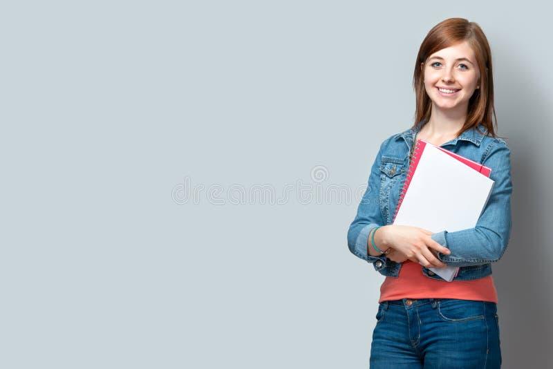 Tiener die zich met boeken bevinden stock foto