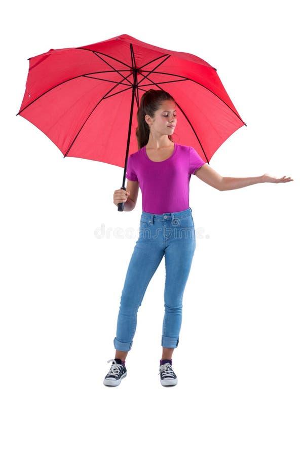 Tiener die zich onder een rode paraplu bevinden royalty-vrije stock afbeeldingen