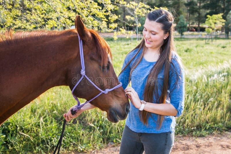 Tiener die zich in openlucht met haar kastanje Arabisch paard bevinden stock foto's