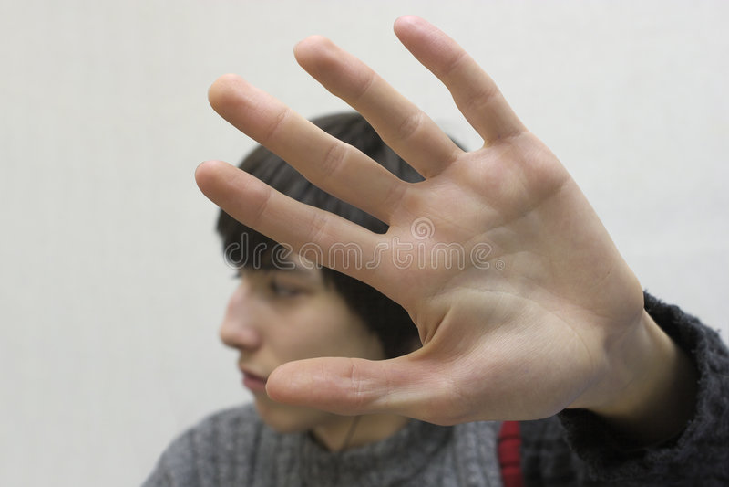 Tiener die zijn gezicht verbergt. stock afbeelding
