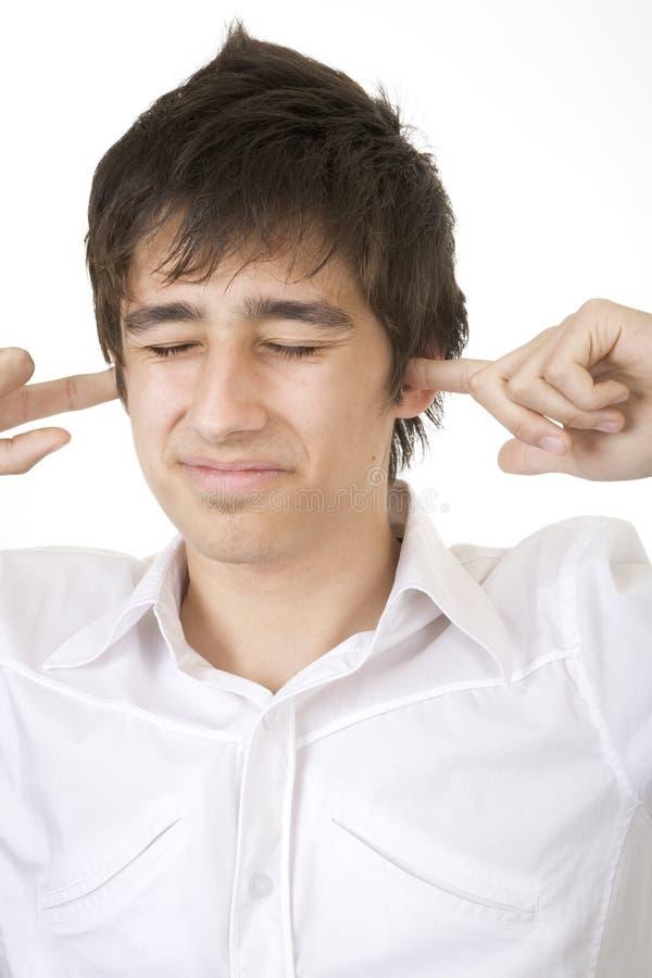 Tiener die zijn oren blokkeert stock foto's