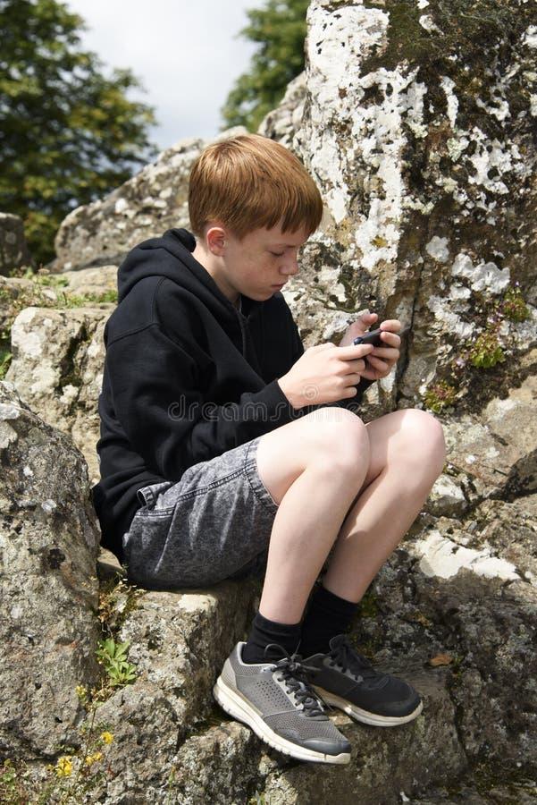 Tiener die zijn slimme telefoon buiten met behulp van royalty-vrije stock foto