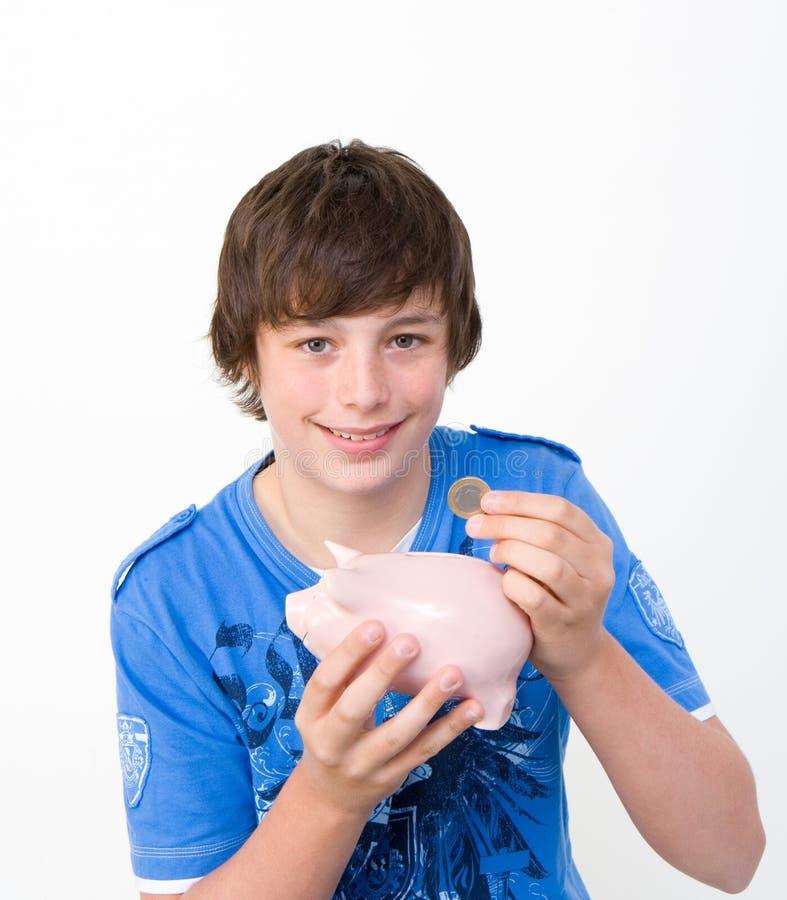 Tiener die zijn spaarvarken vult stock foto