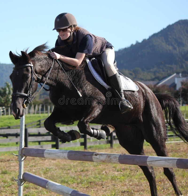 Tiener die zwart paard springen royalty-vrije stock fotografie