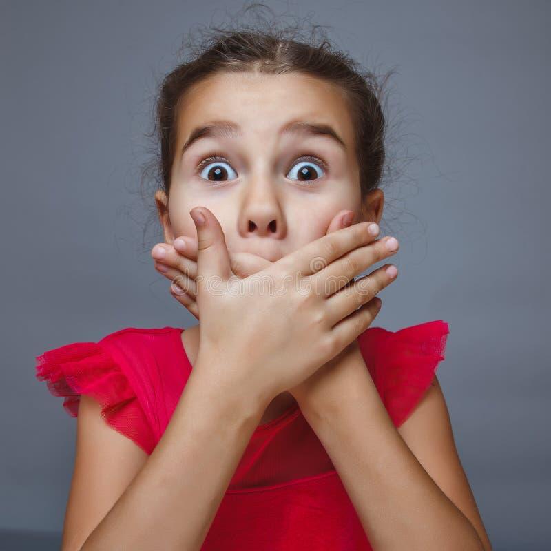 Tiener donkerbruin meisje die mond behandelen met haar handen royalty-vrije stock fotografie