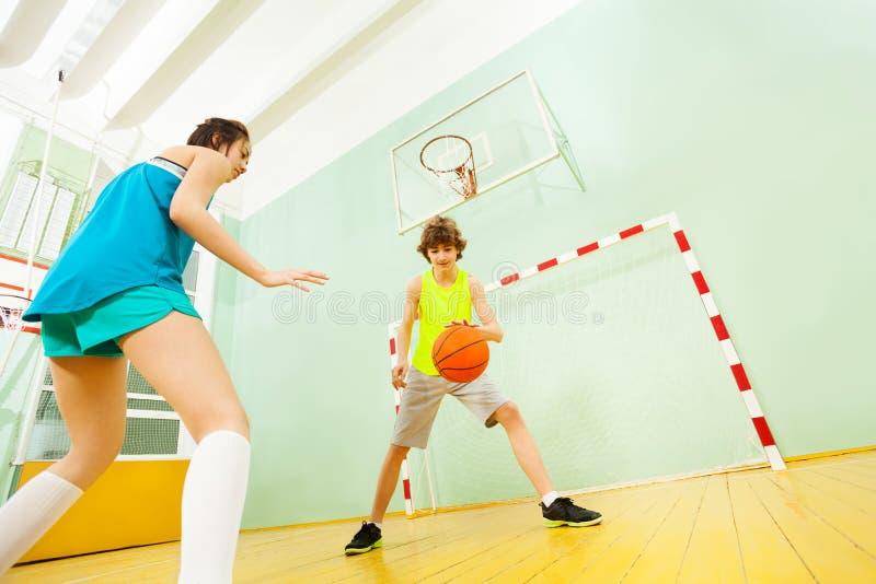 Tiener druppelend basketbal tijdens de gelijke stock afbeeldingen