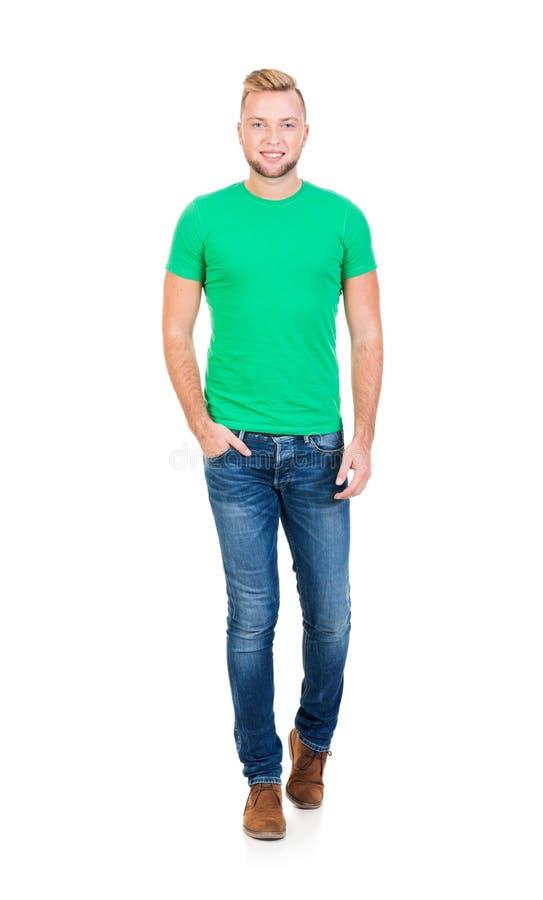 Tiener in een groen overhemd en jeans op wit stock foto