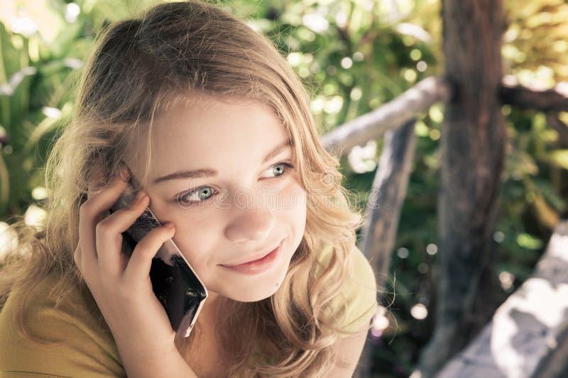 Tiener in een park die op een celtelefoon spreken stock fotografie