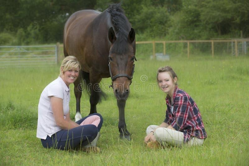 Tiener en haar moeder met haar poney stock fotografie