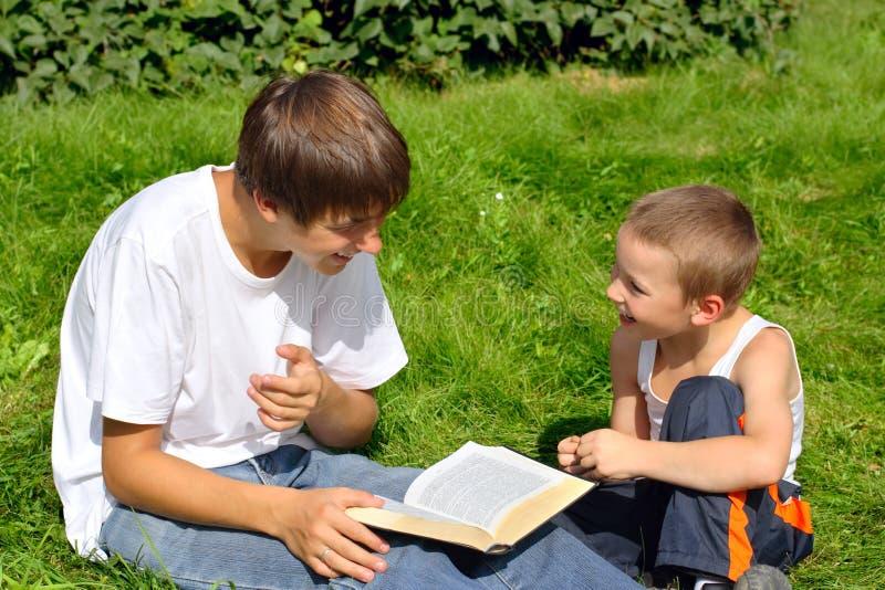 Tiener en jong geitje met een boek stock foto's