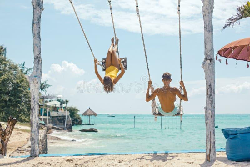 Tiener en jongens het hangen op schommeling met een overzeese mening in strandkoffie stock afbeelding