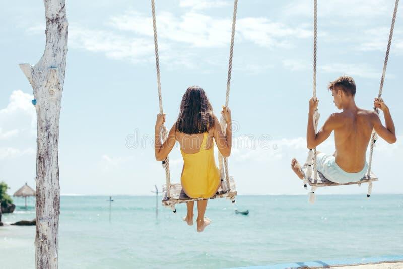 Tiener en jongens het hangen op schommeling met een overzeese mening in strandkoffie royalty-vrije stock foto's