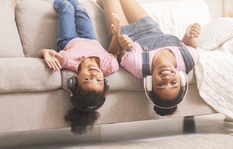 Tiener en kleine zwarte meisjes die van muziek in hoofdtelefoons genieten royalty-vrije stock foto