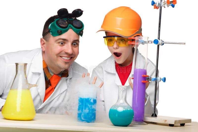 Tiener en leraar van chemie bij les het maken stock afbeelding