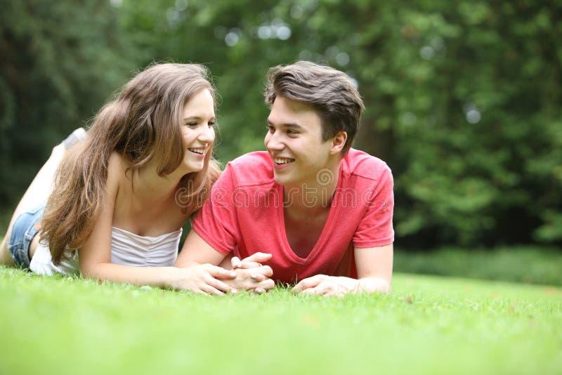 Tiener en meisje die op het gras liggen stock foto