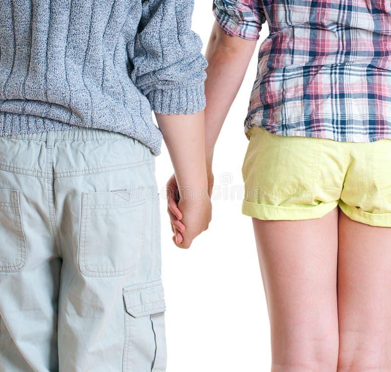 Tiener en meisjesholdingshanden. stock afbeelding