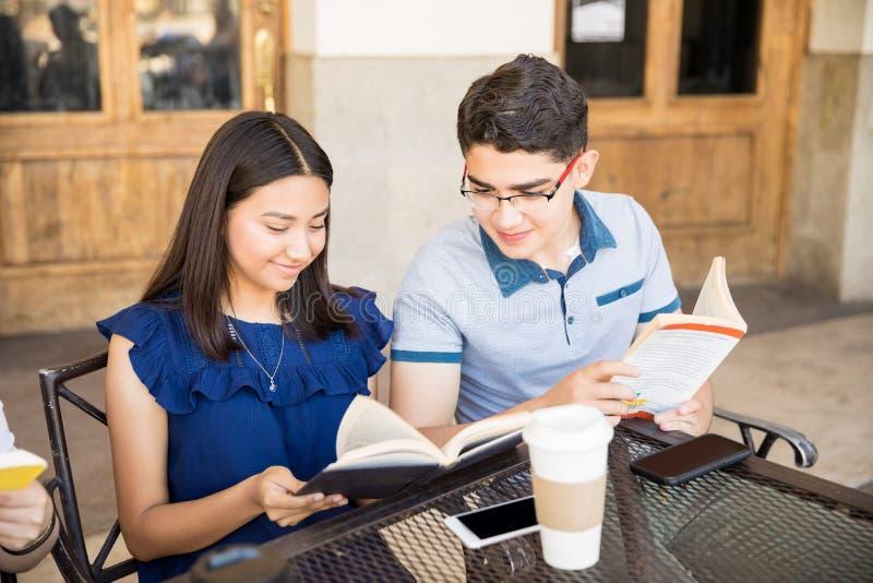 Tiener en meisjeslezingsboeken bij koffie royalty-vrije stock afbeelding