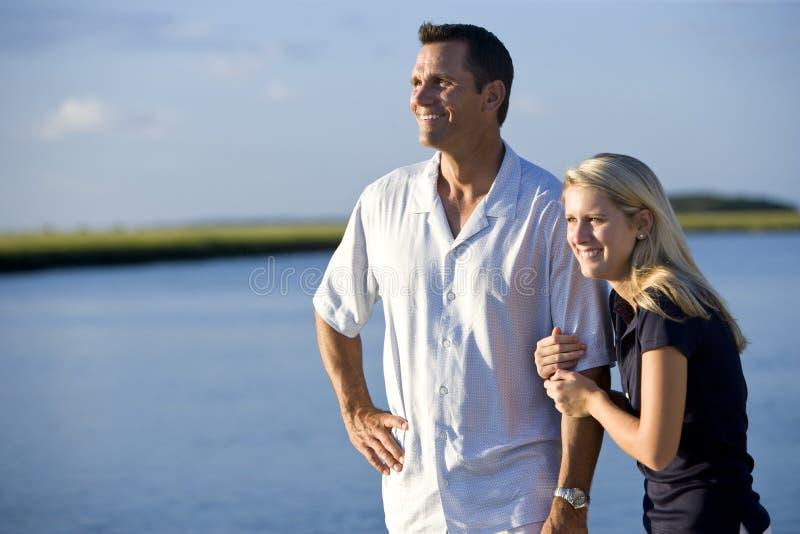 Tiener en vader die zich door water te letten op bevinden stock fotografie