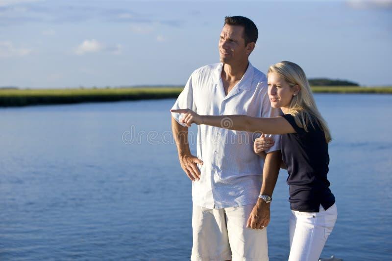 Tiener en vader die zich door water te letten op bevinden royalty-vrije stock afbeelding