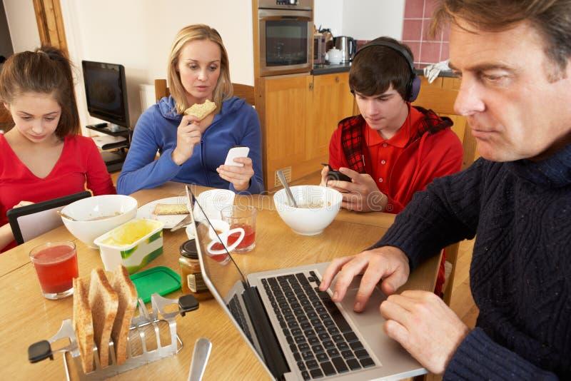 Tiener Familie die Gadgets gebruikt terwijl het Eten stock afbeeldingen