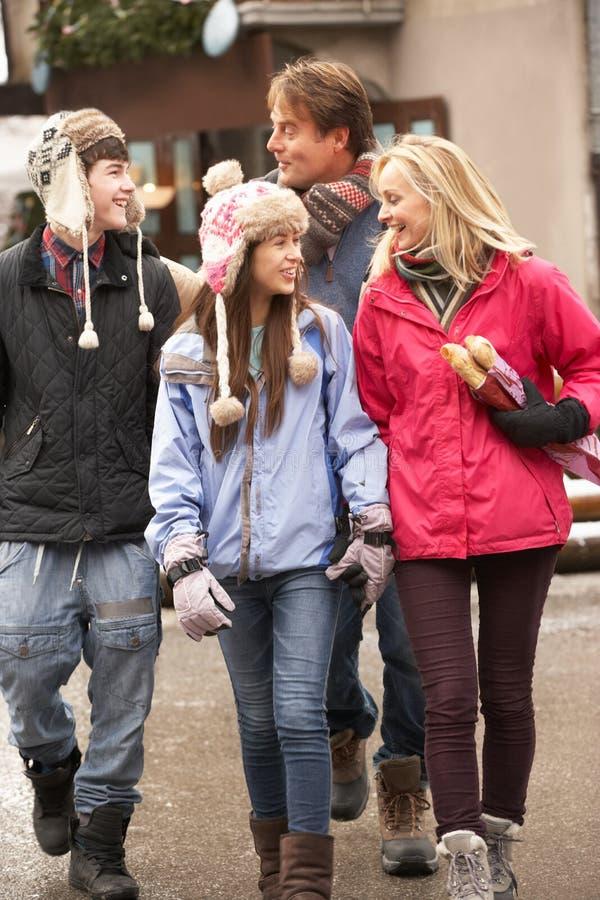 Tiener Familie die langs SneeuwStraat loopt stock foto