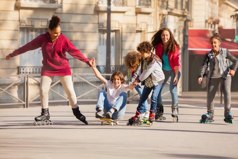 Tiener gealigneerde schaatsers en skateboarder het hebben van pret royalty-vrije stock foto's