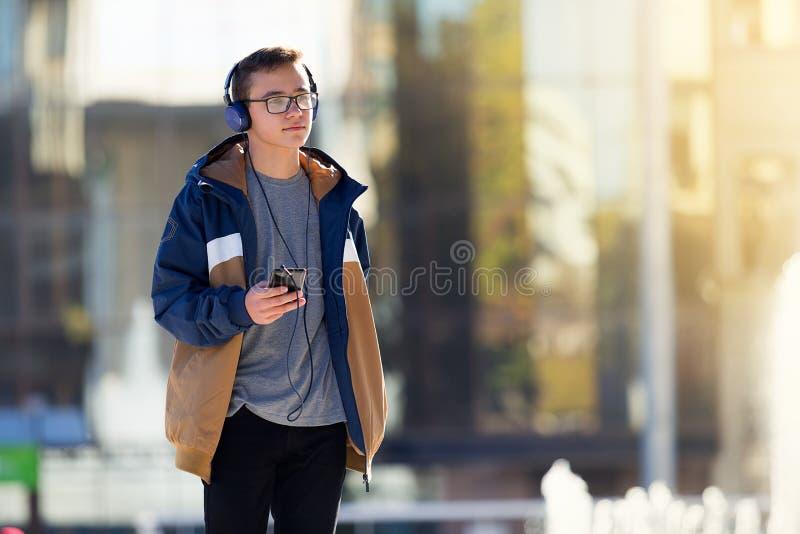Tiener gebruikend smartphone en in openlucht luisterend aan muziek De ruimte van het exemplaar stock afbeeldingen