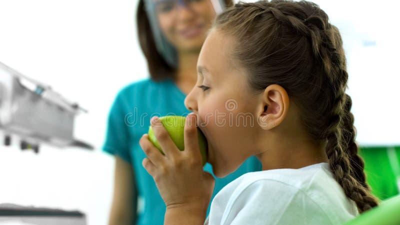 Tiener het bijten appel in de stomatologiebureau, tandarts die bij achtergrond glimlachen stock fotografie