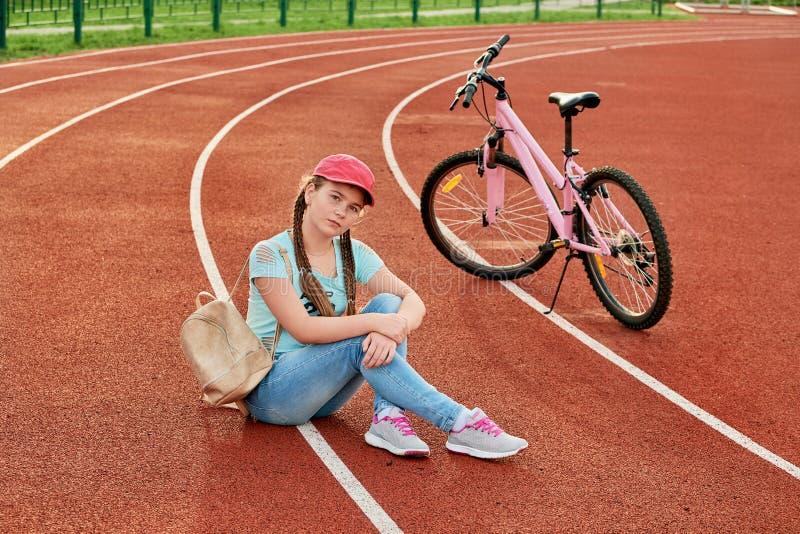 Tiener het ontspannen op een stadion De tiener ontspant met de fiets royalty-vrije stock foto