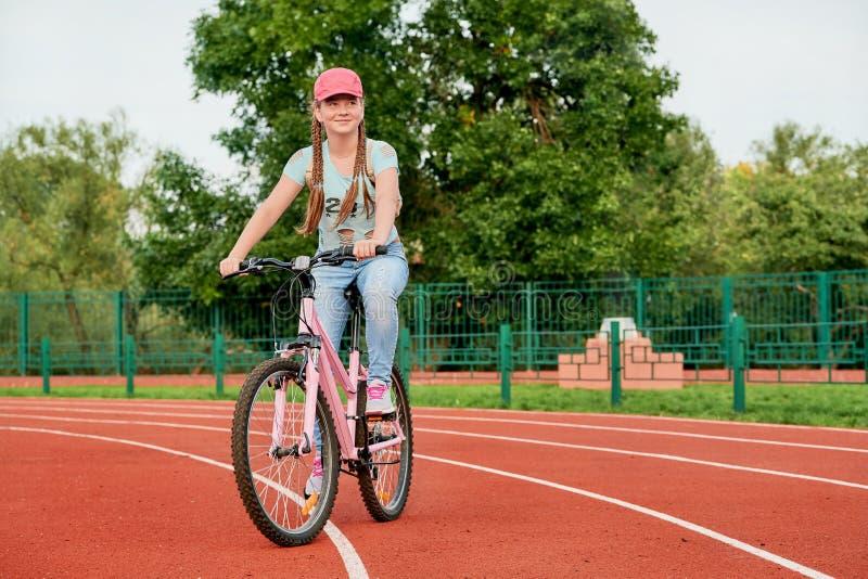 Tiener het ontspannen op een stadion De tiener ontspant met de fiets stock fotografie