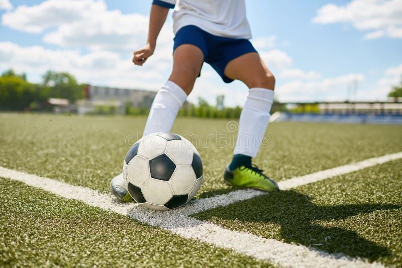 Tiener het Schoppen Bal op Voetbalgebied stock fotografie