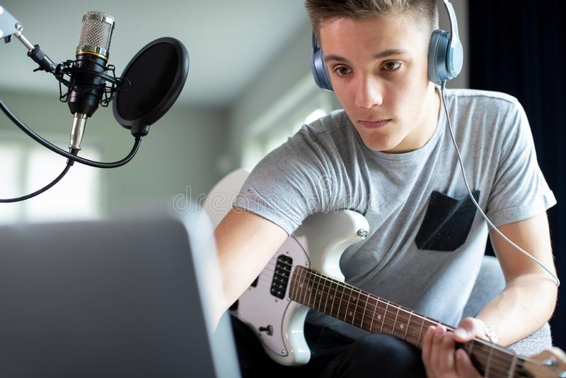 Tiener het Spelen Gitaar en het Registreren Muziek op Laptop thuis royalty-vrije stock foto