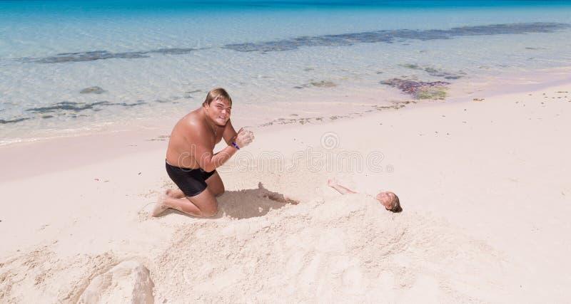 Tiener het spelen met meisje op tropisch mooi strand dichtbij de oceaan royalty-vrije stock afbeelding