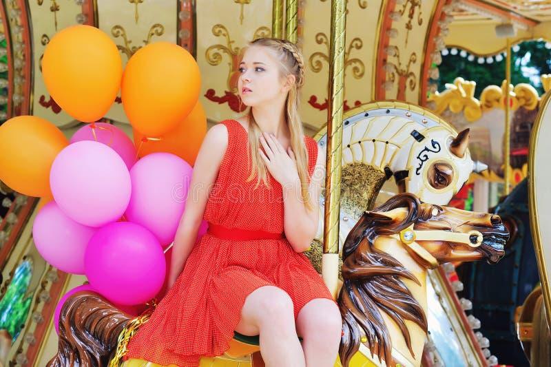 Tiener het stellen op een carrousel stock fotografie