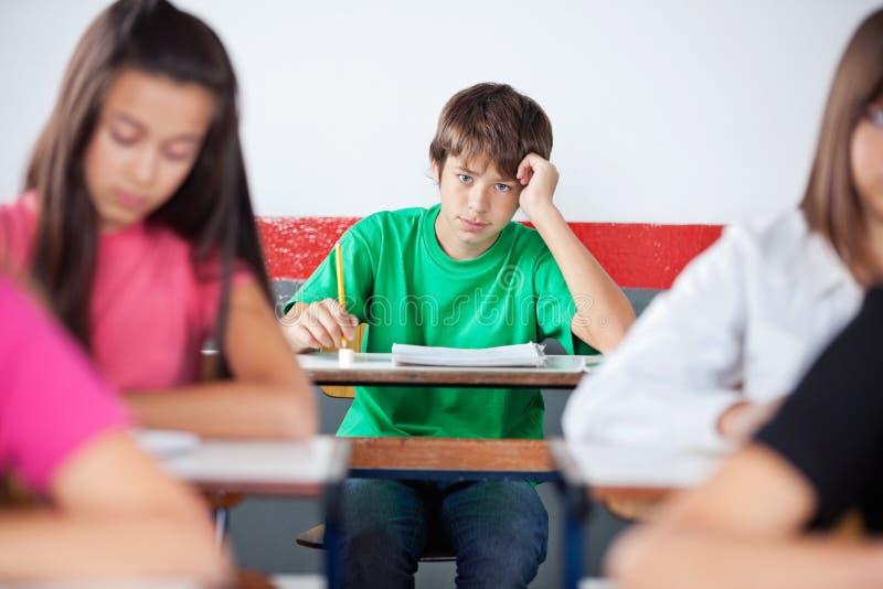 Tiener Mannelijke Student Leaning On Desk bij Klaslokaal royalty-vrije stock foto's