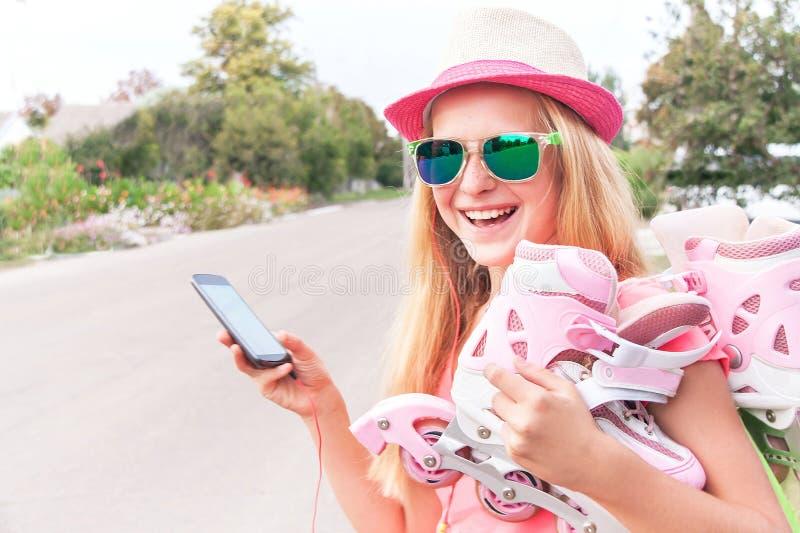 Tiener (meisje) met rol het schaatsen schoenen die slimme telefoon met behulp van royalty-vrije stock foto