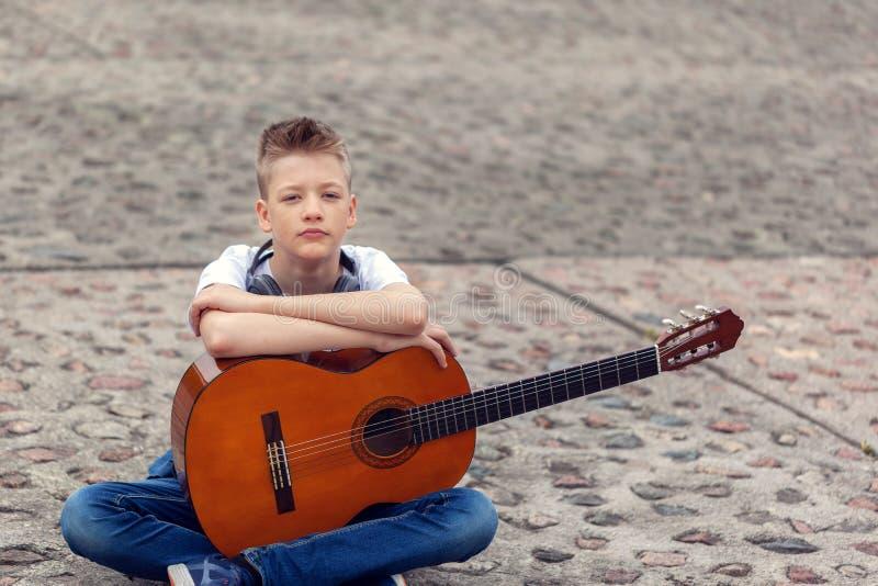 Tiener met akoestische gitaar en hoofdtelefoons die in het park zitten royalty-vrije stock afbeelding