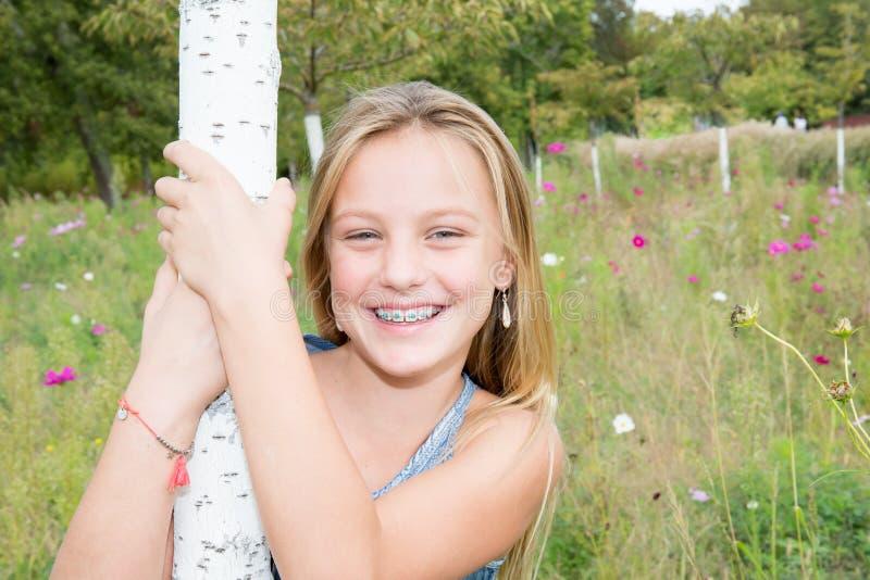 Tiener met blond lang haar en grote blauwe ogen die zich voor groen bevinden stock foto