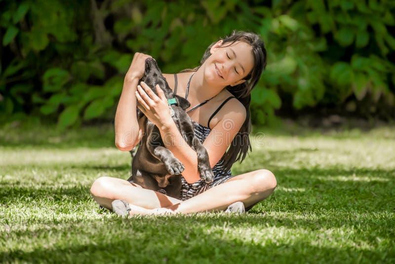 Tiener met buiten het puppy van Labrador stock afbeelding