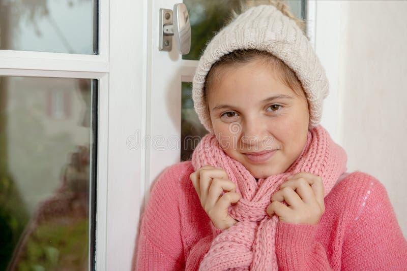 Tiener met een roze sweater en een hoed stock foto's